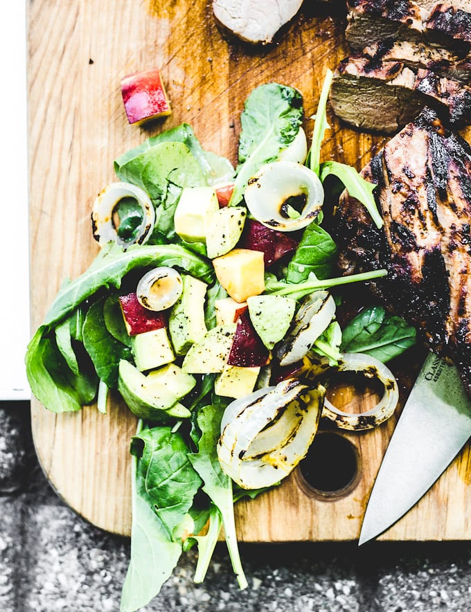 grilled pork tenderloin with wilted greens, sweet onions + peach vinaigrette | theclevercarrot.com