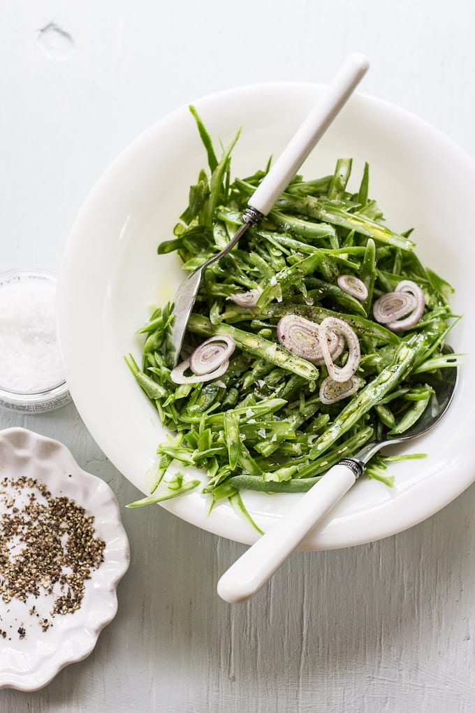 French cut green beans in a bowl with shallots.