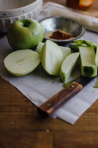 Chunks of Granny Smith Apples with a knife on a cutting board