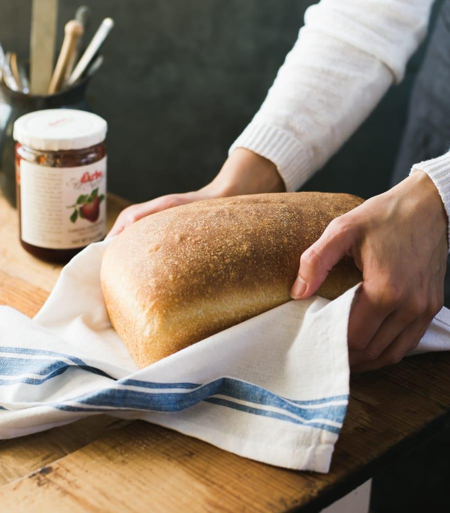 Loaf of sourdough sandwich bread, wrapped in a tea towel, in a baker's hands