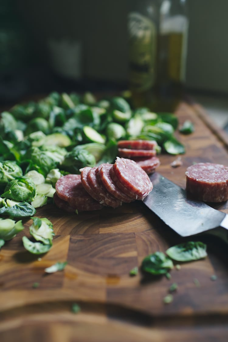 Brussels sprouts and salami on a cutting board
