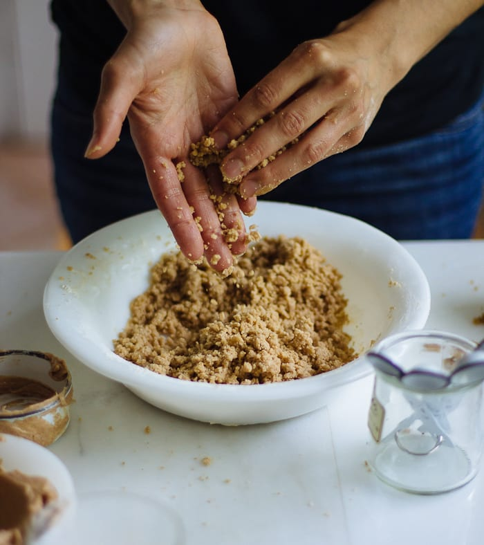 Hands rubbing crumble topping ingredients together