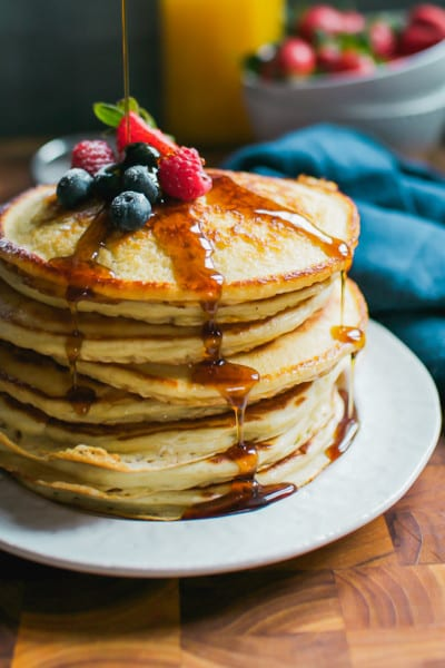 Stack of Fluffy Sourdough Pancakes with maple syrup and fruit