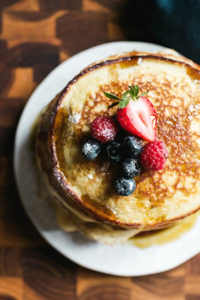 Stack of light and fluffy sourdough discard pancakes with fruit on top