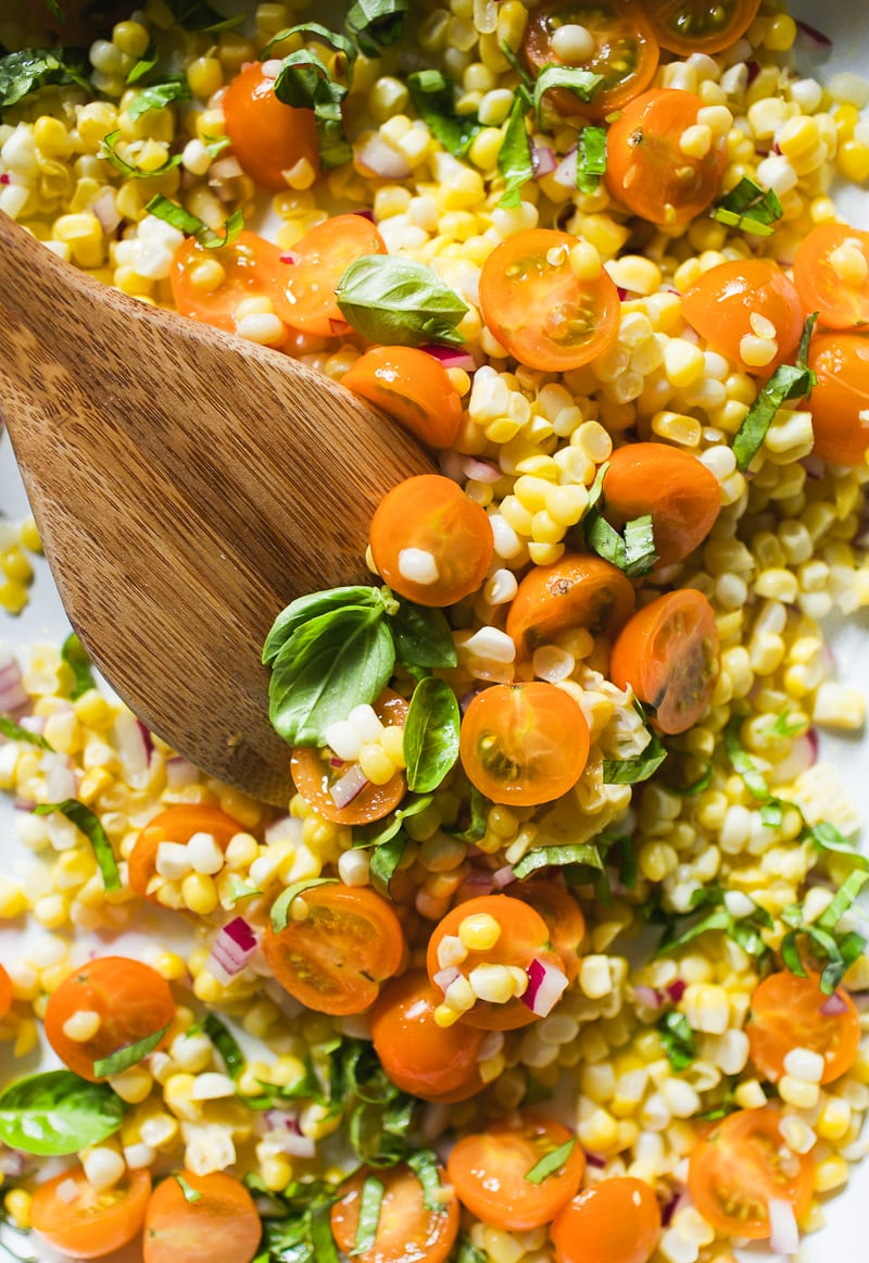 Close up of fresh corn kernels, sun gold cherry tomatoes, red onion and basil in a dish.