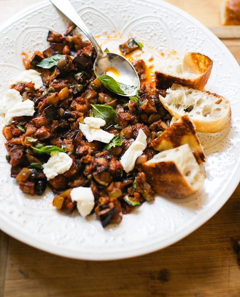 Sicilian caponata on a white plate with fresh mozzarella, basil, sliced focaccia and a spoon.