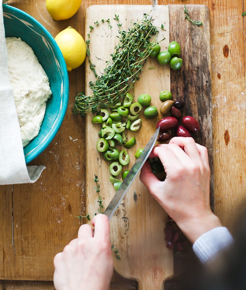 Cutting board of chopped olives and thyme