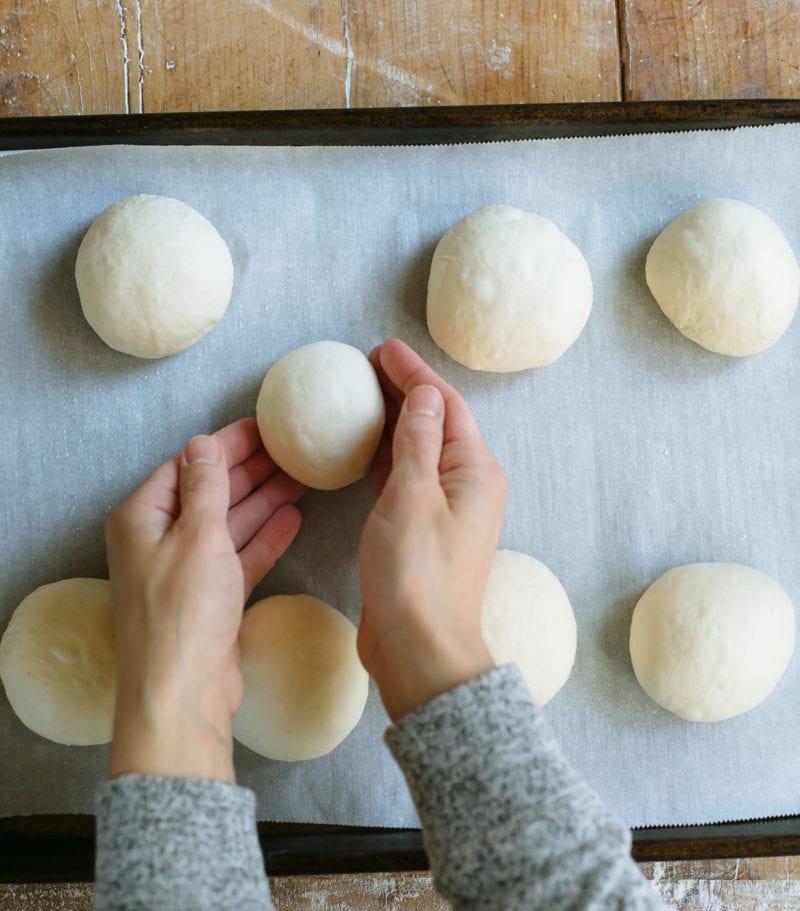 Balls of sourdough bagel dough on a parchment lined sheet pan