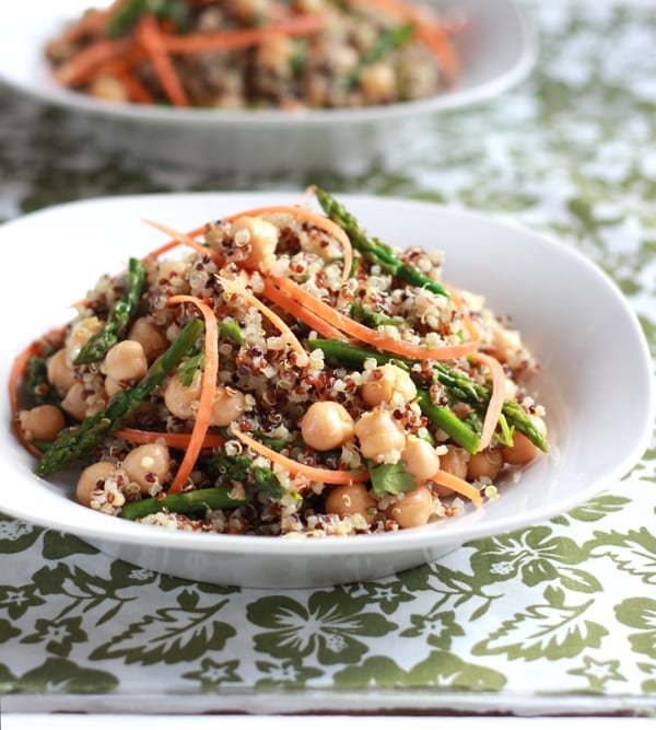 White bowl of curried quinoa with asparagus, chickpeas and shredded carrots.