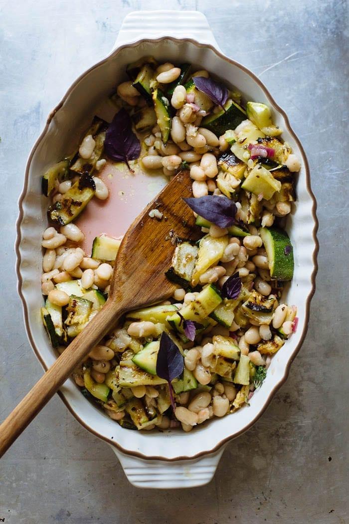 Dish of white beans, grilled zucchini and vinaigrette.