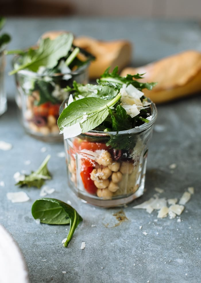 Kale salad with chickpeas, tomatoes and olives in small individual jars.
