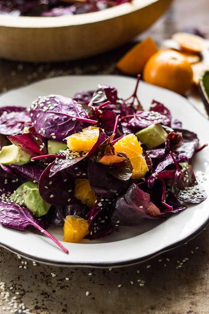 Plate of red heirloom spinach leaves, sesame seeds, orange segments and chopped avocado.