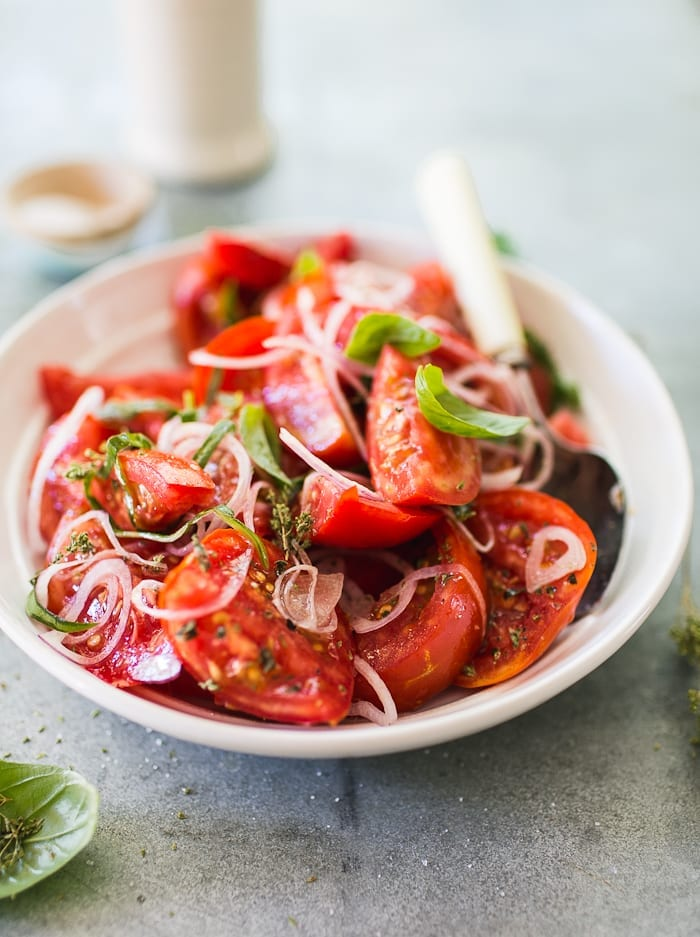 Bowl of juicy red tomato wedges with shaved onion and herbs.