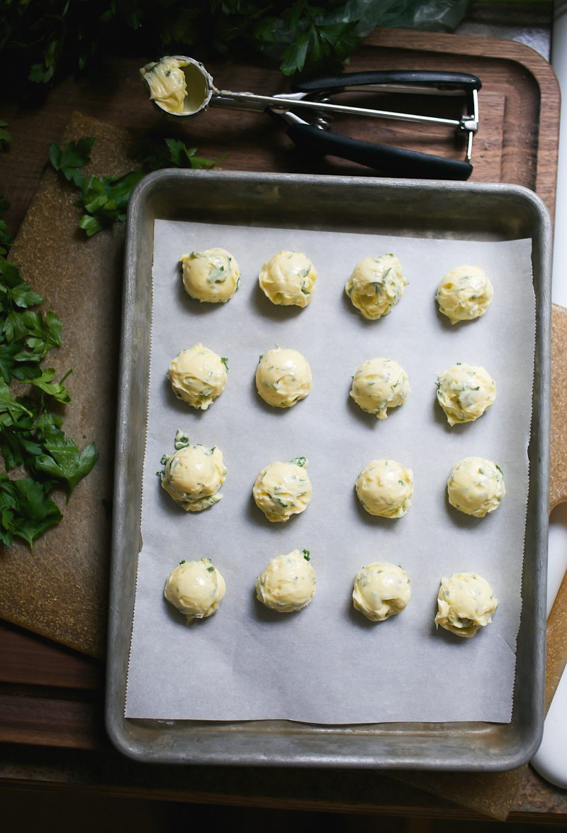 Sheet pan with tablespoon-size portions of scooped garlic butter.