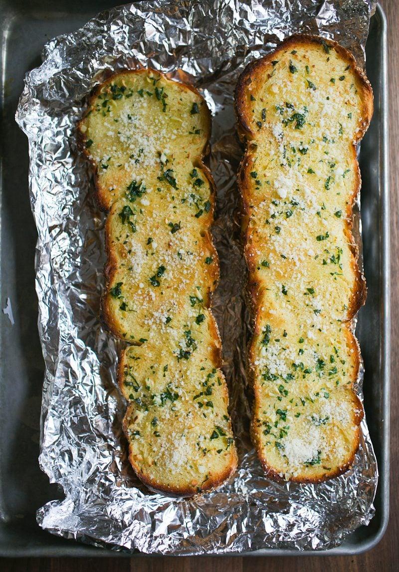 Cut halves of sesame semolina garlic bread, baked, on a foil lined sheet pan.