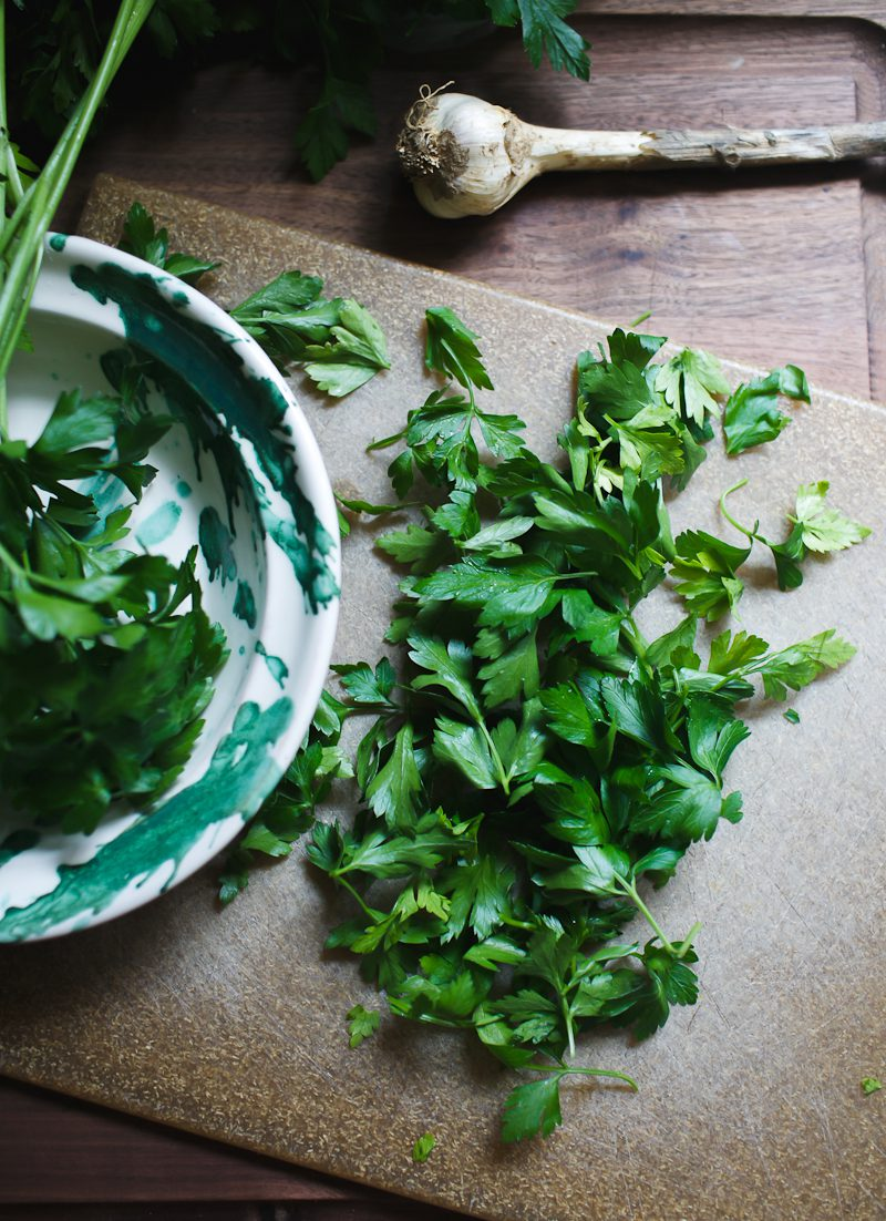 Brown cutting board with chopped parsley and garlic.