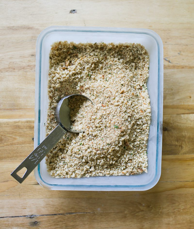 Seasoned sourdough breadcrumbs in a rectangular baking dish with a measuring scoop